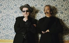 Elvis Costello and Allan Toussaint, against lovely wallpaper