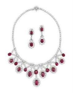 A SET OF RUBY AND DIAMOND JEWELRY, BY VAN CLEEF & ARPELS Comprising a necklace, designed as seven graduated oval and circular cabochon ruby and circular-cut diamond cluster pendants with cabochon ruby and four-stone diamond collet V-shaped spacers, to the circular-cut diamond neckchain; and a pair of ear pendants en suite, 15 1/2 ins.
