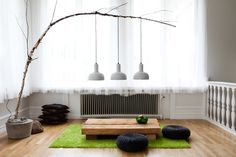 Idha Lindhag - white sheer curtains, tree branch light, green shag rug, low wood beam table, poufs