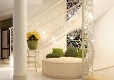 La ringhiera in ferro battuto con motivo a rami intrecciati della scala curva crea una nicchia ideale per collocare un divano tondo
