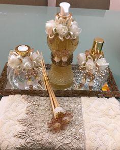 Kit lavabo  1 sabonete líquido 250ml(cinturinha)  1 Difusor 200ml (Morango)  1 Home spray 170ml(bico de jaca)  1 conjunto com 4 varetas (sendo 2 decoradas).  Flores na cor marfim + tampas douradas e cordão de perolas.  *nao inclui bandeja.  Caso queira adquirir solicite.  Bandeja 68,90  Toalha 38... Bottles And Jars, Perfume Bottles, Pots, Altered Bottles, African Jewelry, Snow Globes, Diy And Crafts, Candle Holders, Baby Shower