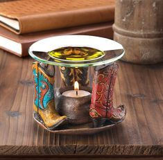 Western flair and fresh aroma will be yours with this charming oil warmer. The base features three intricately detailed cowboy boots set around the brim of a well-worn cowboy hat that's ready for the tealight candle of your choice. Fill the glass basin on top with scented oil.