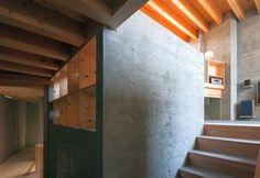 Cemento grezzo e legno non trattato creano il caldo involucro di Shrimp House. La villa ha il soffitto con travi a vista