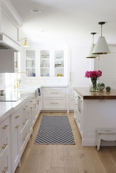 A classic white kitchen remodel with wood countertop island and brass hardware…