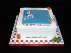"""Swimming Pool Cake - Swimming pool for a competitive swimmer. I was asked for the swimmer to have a red and white cap and for there to be orange floats and green flippers by the pool. 8"""" square vanilla sponge with jam and buttercream, covered with marzipan and sugarpaste, with piping gel for the wet look of the water!"""