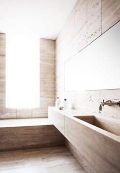 Modern restroom with floor to ceiling stone and a large window