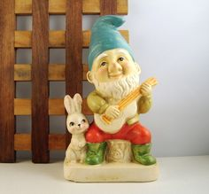 happiness is a gnome on a stump playing the ukulele with a bunny rabbit by his side