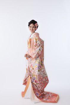 淡いサーモンピンクのグラデーションの上に散りばめられた花々が可愛らしい一着。柔らかい印象の色打掛なので、ふんわりとした洋髪等がよく似合う。