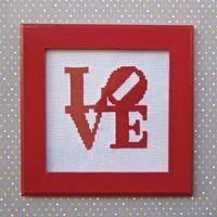 Quadro Love - R$ 100,00  Quadro em MDF com moldura vermelha e vidro. Possui suporte para fixação em parede e acompanha suporte para mesa. Bordado em ponto cruz artesanal.  Dimensões (com moldura) 21cm (altura) x 21cm (larura) x 1,5cm (profundidade)