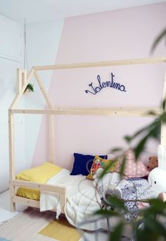 DIY : Un lit cabane pour une chambre d'enfant / blush pink and white diagonal wall in little girls room with DIY wood house frame bed and yellow bedding.