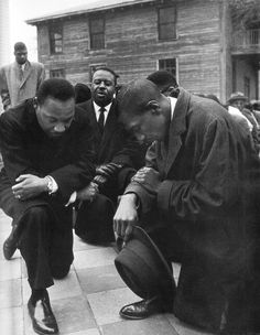 """Dr. Martin Luther King Jr, praying with some of his fellow civil rights activists as they prepare to peacefully march on 1 February 1965 (subsequently known as """"Bloody Sunday"""") in Selma, Alabama."""