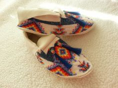 Native American fully beaded moccasins finished in 9/0 cut glass beads with blue horse hair. Find this pair and others like it for sale on our website at www.sharpsindianstore.com