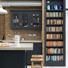Amazing kitchen with black cabinets, chunky concrete worktop, exposed brick and a bookcase | deVOL kitchens