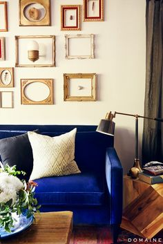 Ian Harding's Los Angeles living room has vintage charm with a gallery wall of empty gold frames and a cozy blue velvet sofa