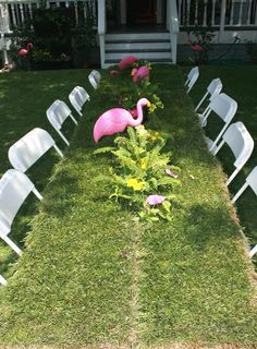 Flowers, flamingos and sod cover this table for a pretty garden party.