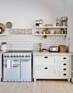 If you're lacking on storage space in the kitchen, a few shelves can go a long way. Here, metallic tones combine with the cream colour scheme to create a country kitchen with a modern edge