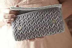 Dropped double treble crochet stitches form this textured chevron pattern. A simple fabric lining hides the plastic canvas that gives this crochet clutch its sleek and sturdy shape. Magnetic snaps keep the flap in place, and large decorative buttons add modern style.