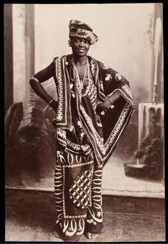 Swahili woman posing with arms akimbo, flamboyantly dressed in printed kangas and turban and wearing jewelry, Zanzibar