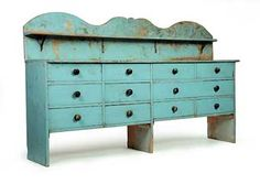 "APOTHECARY OR HARDWARE CHEST WITH OVERSHELF, American, 19th century, pine. Twelve dovetailed drawers in a case on solid board ends with old blue paint. 37""h. 92""w. 18""d. With a pine overshelf. 17.5""h. 92""l. Sold at Garth's Auction March 16, 2013."