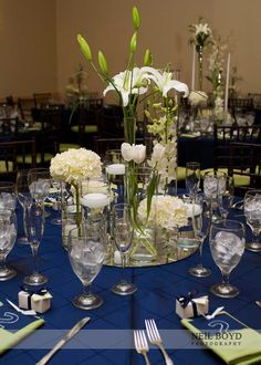 Blue table linens with green accent color.  Multi vase & white floral centerpiece