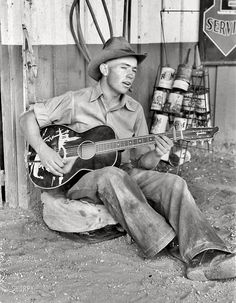 """June 1940. Pie Town, New Mexico. """"Farm boy playing guitar in front of the filling station and garage."""" 35mm nitrate negative by Russell Lee"""