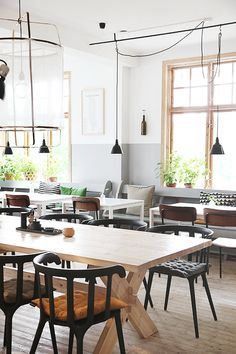 Black Ikea PS 2012 chairs and white Melltorp tables mixed with vintage and designer pieces in a Swedish restaurant.