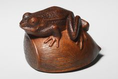 Artist: Sukenaga School: Hida Date: Circa 1830 A frog crouches on a chestnut, its extended back leg and alert pose conveying a sense of watchful tension, the creature poised to leap forward at a moment's notice. The pocked texture of the skin is intricately carved, as the is the rough scar of the chestnut where it once attached to its seed pod, which is rendered in ukibori. Signed: Sukenaga. Length: 4.0cm