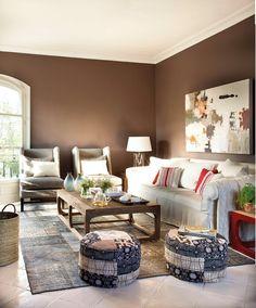 Auxiliares versátiles y color Las interioristas Mar y Cristina Barroso han combinado un sofá con dos butacas y dos pufs.