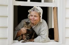 Woman and her cat at the George Wythe House Kitchen window.