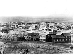 Tombstone, Arizona in 1881 photographed by C. S. Fly. An ore wagon at the center of the image is pulled by 15 or 16 mules leaving town for one of the mines or on the way to a mill. The town had a population of about 4,000 that year with 600 dwellings and two church buildings. There were 650 men working in the nearby mines. The Tough Nut hoisting works are in the right foreground. The firehouse is behind the ore wagons, with the Russ House hotel just to the left of it.