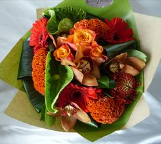 A tropical style handtied bouquet of #Gerberas, #Roses, #Orchid Heads, #Pincushions, #Celosia and #Anthuriums in vibrant reds, oranges and greens. Tropical Style, Pincushions, Orchid, Bouquets, Roses, Vibrant, Seasons, Table Decorations, Flowers