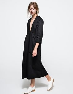 From Toit Volant, a mid-weight slip on dress with modern design in black. Features plunging neckline, long sleeves, two front pockets, cuffed sleeves, finished edges, full length, flared hem and relaxed fit.  • Mid-weight slip on dress in black • Plung