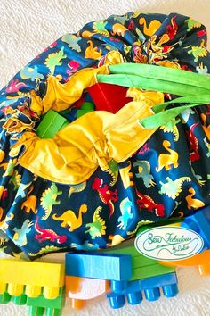 Trying to maintain a little more sanity with at home? | let this toy storage bag be your new tool for keeping things tidy! | putting the fun in functional design with a brightly colored dinosaur design!