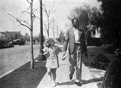 "shirleytemple.com Hand in hand with Uncle Billy ""Bojangles"" Robinson, 1935. (Twentieth Century-Fox)"