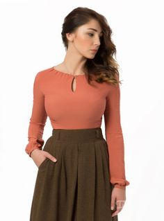 Blouse Assol in Terracotta. Incredibly feminine blouse cut from the tender soft fabric. Frills by the neckline; elegant cut-out-droplet. Long frilled sleeves. Charming small metal buttons; DDAtelier Sizing tip: This blouse runs small. Order a size up. Composition: 50% cotton, 48% viscose, 2% elastane. Length of the product: 60 cm / 23⅗ inches.
