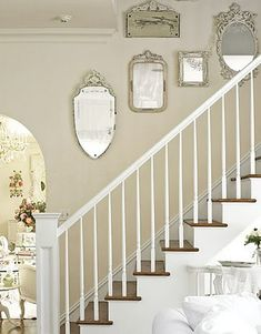 Lovely stairway ~ eclectic wall gallery of mirrors!
