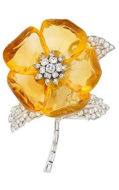 An Art Deco platinum, citrine and diamond flower clip-brooch, French, circa 1930. Composed of overlapping carved citrine petals, centring a cluster of round diamonds atop three leaves and a baguette diamond-set stem, with maker's mark and French export marks. #ArtDeco #ClipBrooch