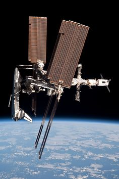 A side-on view of the ISS showing a Space Shuttle docked to the forward end, an ATV to the aft end and Soyuz & Progress spacecraft projecting from the Russian segment.