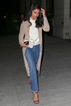 Selena Gomez wearing Jimmy Choo Minnie Sandals in Black, Louis Vuitton Iris Wallet, Wes Gordon Single Breasted Belted Trench Coat, Vetements Blue Raw Hem High Waisted Jeans and Co Ruffled Merino Wool Sweater