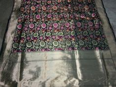 This Pure Katan Banarasi silk saree is one of our favorites. Bordered in zari is a garden in full bloom. On a bed of black the pinks, oranges and greens form a vibrant and stunning color story. This beautiful saree is accompanied with a black blouse.