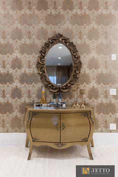 A composição de papel de parede com o espelho de moldura trabalhada e a bombê dourada são a síntese do estilo clássico que permeia toda a decoração.