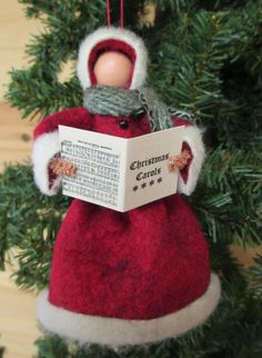 "Christmas Caroler Ornament Handmade by ModerationCorner on Etsy...Christmas Caroler is dressed in an old fashioned fur lined coat of red wool felt with black buttons along the front. Each one carries a miniature Christmas Carol book of actual carols shrunk to size and wears a wool scarf. Actual color or pattern of scarf will vary. Approximate Dimensions: 5 - 5 1/2"" H x 3"" W"