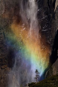 A rainbow emerges from the mist of Yosemite Falls, Yosemite National Park, California...