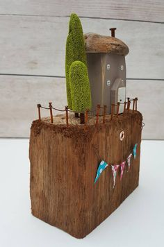 Cute handmade driftwood cottage called looking out to sea. This medium sized work depicts a cottage painted in heritage grey with its tiny windows painted white. There is a little fence outside the cottage and a lifebelt attached to the cliff side. At the front there is a string of