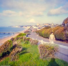 Quaint: A woman walks up a road winding parallel to the seafront at Bournemouth in this stunning picture taken in 1958 Map Of Britain, Battle Of Britain, British European Airways, Car Boot Sale, Uk History, St Ives, Bournemouth, English Countryside, Color Photography