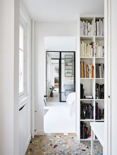 This compact long narrow Paris apartment has been designed to maximise space & light .. even placing a large mirror at the back of the apartment so the line of vision seems to go on. Different floor t