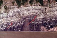 Folded & thrust-faulted shale & limestone of Late Mississippian - Early Pennsylvanian Calico Bluff Formation, on the Alaskan side of the border with Canada, along the Yukon River. Just north of the major strike slip Tintina Fault which makes an old plate boundary between North America and what was the Pacific Ocean.  In the Cretaceous a subduction zone and island arc began implacement of igneous rocks which are now extant south of the Tintina Fault.