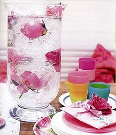 This large hurricane vase makes a spectacular centerpiece for a party. A sheet of clear cellophane, which can be bought from a stationary store or florist, has been crumpled inside the vase. Pink peonies (Paeonia)—which could be replaced by roses (Rosa)—have been tucked down into it before adding water, producing a cracked-ice effect.    Flowers that have been submerged like this won't last as long as those that only have their stems in water, but they should look good for a day or so.