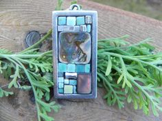 "mosaic pendant in blues w/ large mother of by ClearlyCaroline, $23.00. The focal point is a lovely mother of pearl tile. I also used ceramic tiles and silver accents in a pewter frame.  A 20"" silver chain is also included  Size: 2""x1"". Lightly grouted in charcoal."