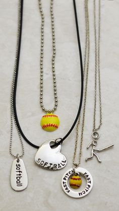 From left to right: SportWORD Softball Necklace, Softball Heart Necklace, Enamel Softball Necklace, Fast Pitch Message Ring Necklace, and Silver Softball Girl (Stick Figure) Necklace.